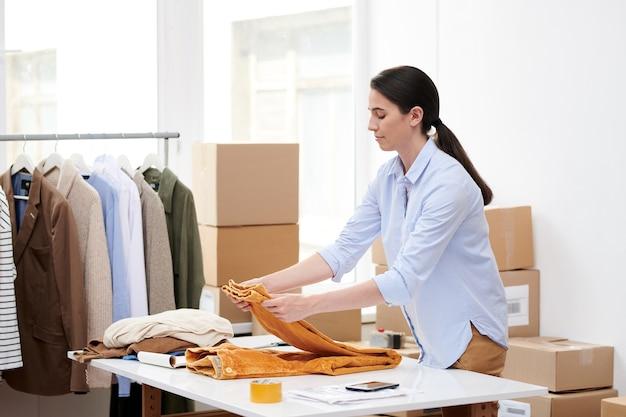 Jovem mulher casual dobrando calças de veludo amarelo na mesa enquanto prepara o pedido do cliente da loja online