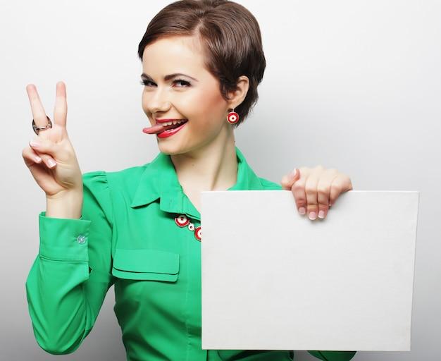 Jovem mulher casual feliz segurando cartaz em branco