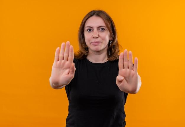 Jovem mulher casual gesticulando para parar e olhando para uma parede laranja isolada com espaço de cópia