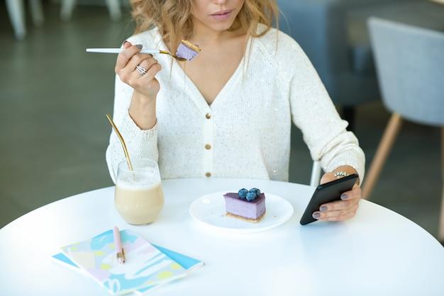 Jovem mulher casual rolando no smartphone enquanto está sentada à mesa no café e comendo um cheesecake de mirtilo
