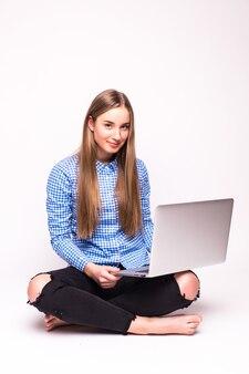 Jovem mulher casual sentada sorrindo segurando um laptop isolado na parede branca