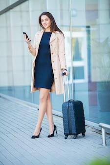 Jovem mulher casual vai no aeroporto na janela com mala esperando o avião