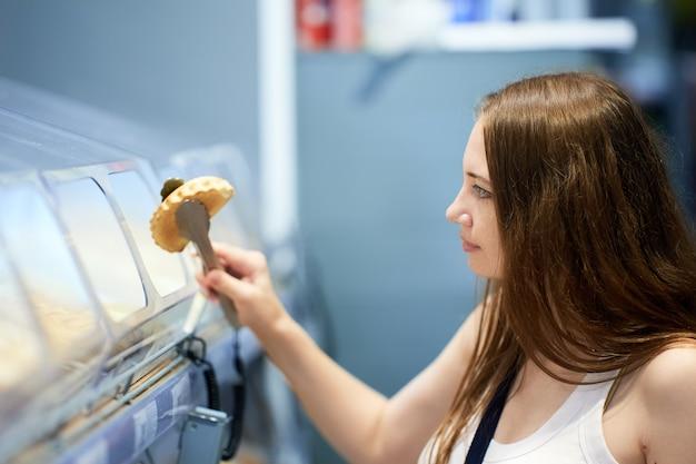 Jovem mulher caucasiana a escolher pastelaria no supermercado
