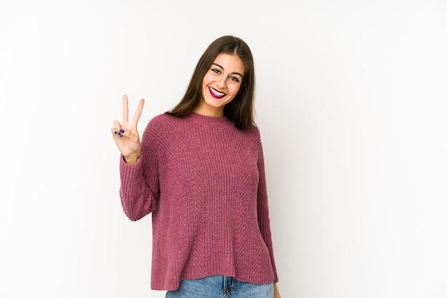 Jovem mulher caucasiana, alegre e despreocupada, mostrando um símbolo de paz com os dedos.