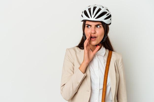 Jovem mulher caucasiana, andando de bicicleta para o trabalho, isolada na parede branca, está contando uma notícia secreta sobre a frenagem e olhando para o lado