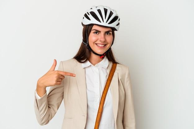Jovem mulher caucasiana andando de bicicleta para trabalhar isolada em um fundo branco pessoa apontando com a mão para um espaço de cópia de camisa, orgulhosa e confiante