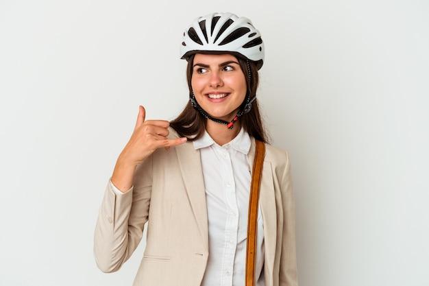 Jovem mulher caucasiana, andando de bicicleta para trabalhar, isolada no fundo branco, mostrando um gesto de chamada de telefone móvel com os dedos.