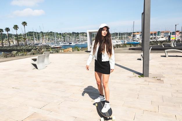 Jovem mulher caucasiana andando de longboard no calçadão
