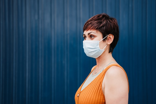 Jovem mulher caucasiana ao ar livre usando máscara facial. conceito de distância social. pandemia durante o vírus corona