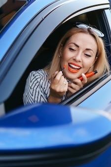 Jovem mulher caucasiana, aplicando o batom, olhando para o reflexo no espelho do carro.