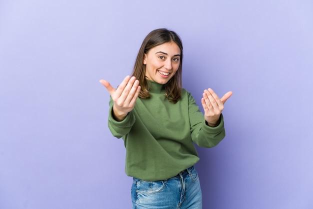 Jovem mulher caucasiana, apontando com o dedo para você como se fosse um convite para se aproximar.