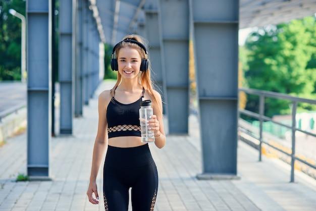 Jovem mulher caucasiana bebe água e ouve música após o treino.