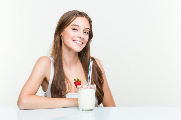 Jovem mulher caucasiana, bebendo um smoothie