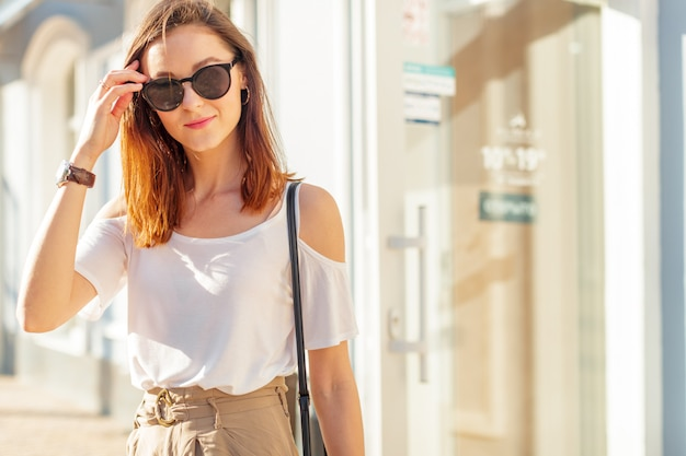 Jovem mulher caucasiana bonita posando ao ar livre na cidade