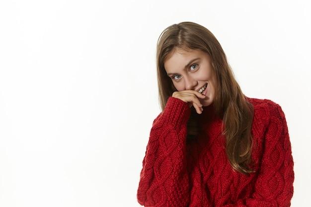 Jovem mulher caucasiana brincalhona e sedutora, vestindo um elegante suéter de malha de manga comprida, sorrindo alegremente, segurando a mão nos lábios, posando