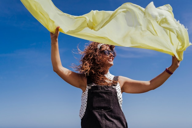 Jovem mulher caucasiana, brincando ao ar livre com lenço amarelo em um dia ventoso e ensolarado. estilo de vida e verão