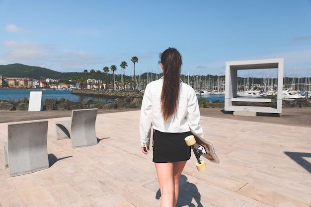 Jovem mulher caucasiana carregando um longboard à beira-mar