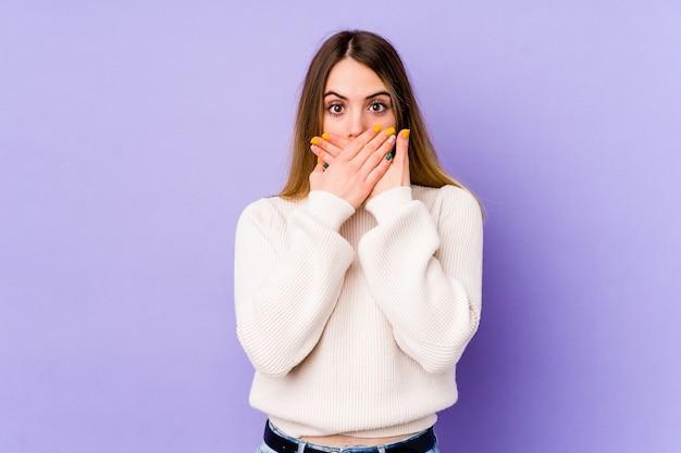 Jovem mulher caucasiana chocada, cobrindo a boca com as mãos.