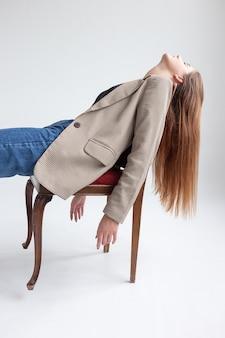 Jovem mulher caucasiana com cabelo comprido deitada na cadeira do estúdio com o queixo para cima