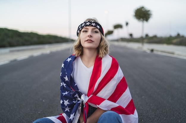 Jovem mulher caucasiana com cabelo loiro curto e uma bandeira dos eua sentada na estrada