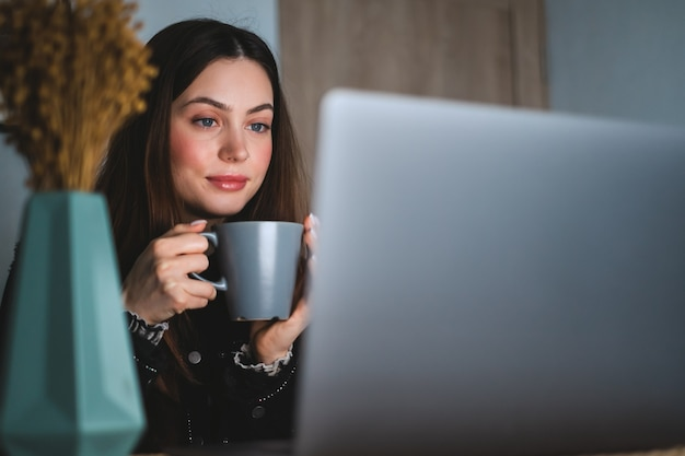 Jovem mulher caucasiana com cabelos castanhos, descansando em casa em um ambiente aconchegante, bebendo chá, sentada em frente ao laptop e olhando para a tela