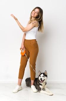 Jovem mulher caucasiana com cachorro sobre parede isolada