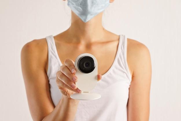 Jovem mulher caucasiana com câmera de segurança e máscara médica facial. triagem de temperatura covid-19