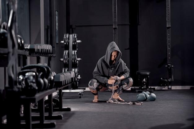 Jovem mulher caucasiana com capuz agachado com os pés descalços e colocar ataduras por lado. ao lado de suas luvas de boxe. conceito de treino à noite.