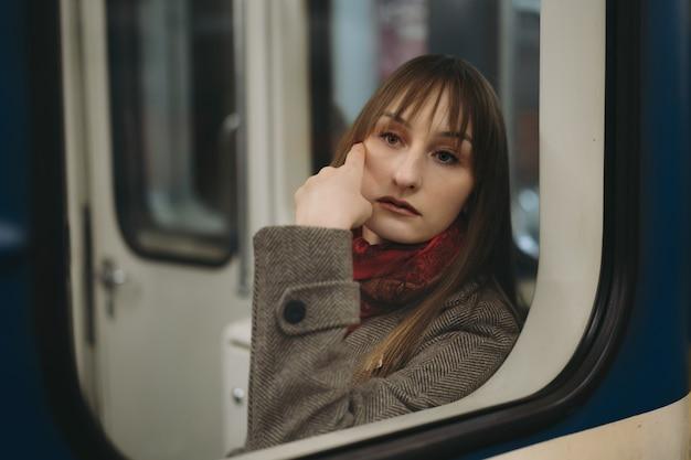 Jovem mulher caucasiana com casaco sentada sozinha no vagão do metrô olhando sonhadoramente para o lado