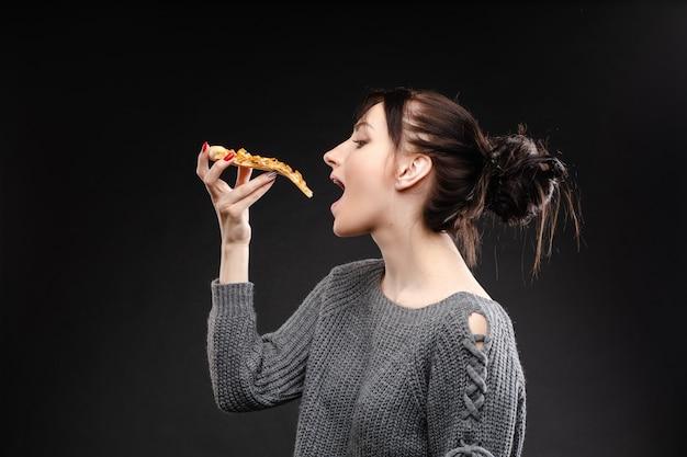 Jovem mulher caucasiana com cauda comendo pedaço de pizza.