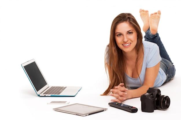 Jovem mulher caucasiana com dispositivos eletrônicos