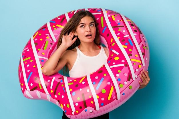 Jovem mulher caucasiana com donut inflável isolado em um fundo azul, tentando ouvir uma fofoca.