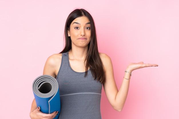 Jovem mulher caucasiana com esteira isolada na parede rosa, tendo dúvidas com a expressão do rosto confuso