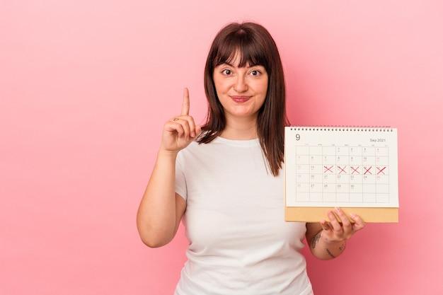 Jovem mulher caucasiana com excesso de peso, segurando o calendário isolado no fundo rosa, mostrando o número um com o dedo.