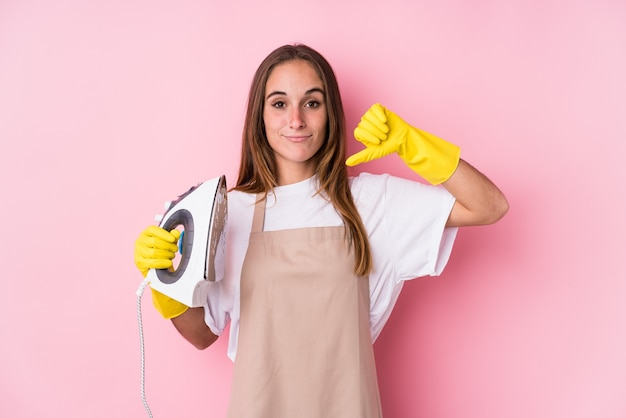 Jovem mulher caucasiana com ferro de passar roupas isolado, mostrando um gesto de antipatia, polegares para baixo. conceito de desacordo.