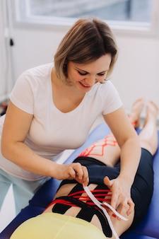 Jovem mulher caucasiana com fita cinesiologia na barriga dela.