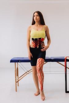 Jovem mulher caucasiana com fita cinesiologia na barriga e na perna.