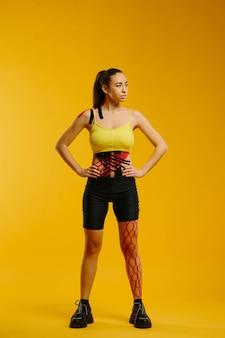 Jovem mulher caucasiana com fita de cinesiologia na barriga e perna, em amarelo