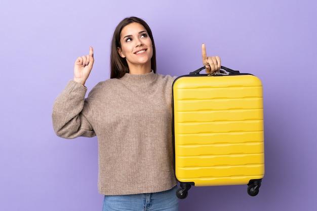 Jovem mulher caucasiana com mala de viagem e apontando para cima