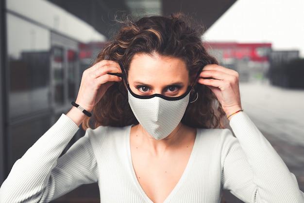 Jovem mulher caucasiana com máscara branca na rua