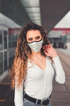 Jovem mulher caucasiana com máscara em área urbana