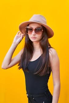 Jovem mulher caucasiana com óculos de sol de cabelo comprido, chapéu bege, regata e calça preta, segurando o chapéu com uma mão