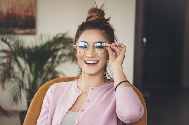 Jovem mulher caucasiana com óculos e suéter rosa, sentada na poltrona e sorrindo