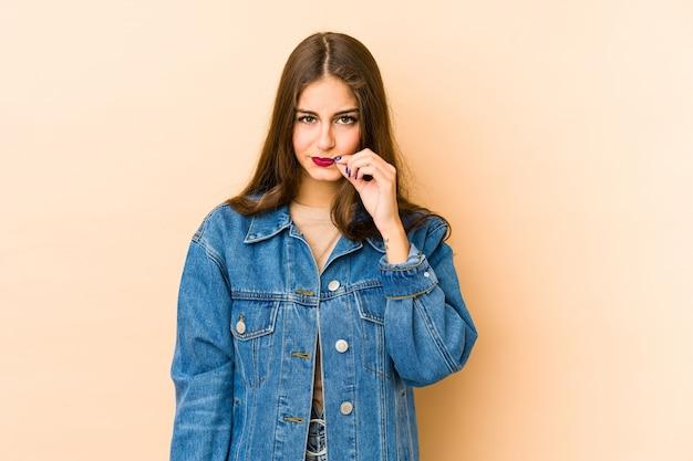 Jovem mulher caucasiana com os dedos nos lábios, mantendo um segredo.