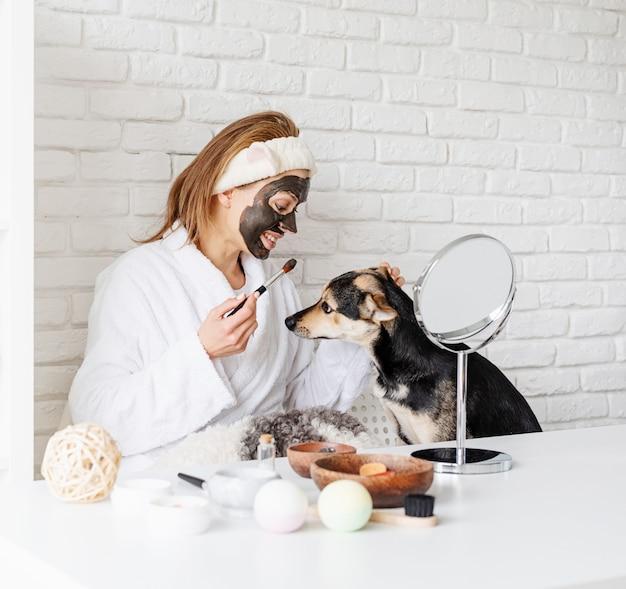 Jovem mulher caucasiana com roupão de banho fazendo procedimentos de spa com seu cachorro