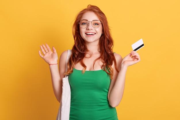 Jovem mulher caucasiana com sacola de compras e cartão de crédito em branco, posando com as mãos espalmadas e expressão facial animada