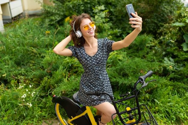 Jovem mulher caucasiana com sorriso perfeito, lábios carnudos, óculos, fones de ouvido, anda na natureza, andar de bicicleta e grava um vídeo, fazer selfie
