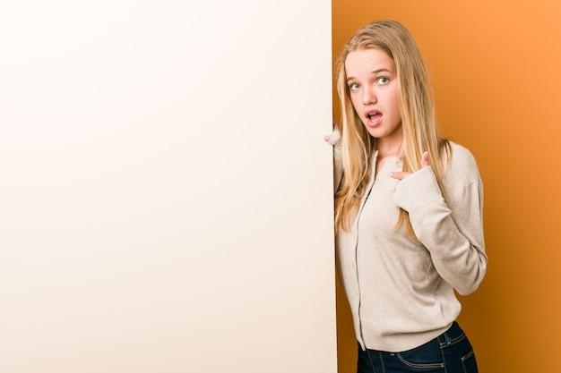 Jovem mulher caucasiana com surpresa apontando para si mesmo, sorrindo amplamente.