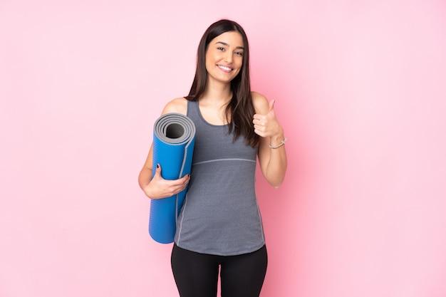 Jovem mulher caucasiana com tapete isolado na parede rosa dando um polegar para cima gesto