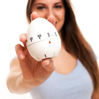 Jovem mulher caucasiana com timer de cozinha